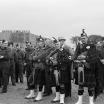 Group of men standing with three in centre wearing kilts & tartans holding bag pipes.