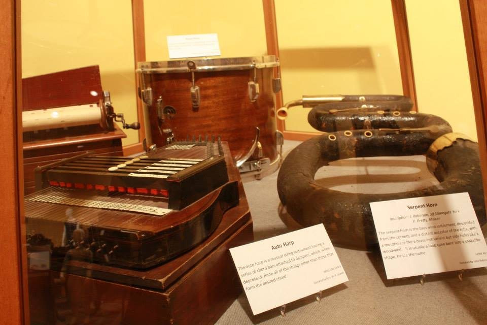 Display case with an accordian, drum, and serpent horn.