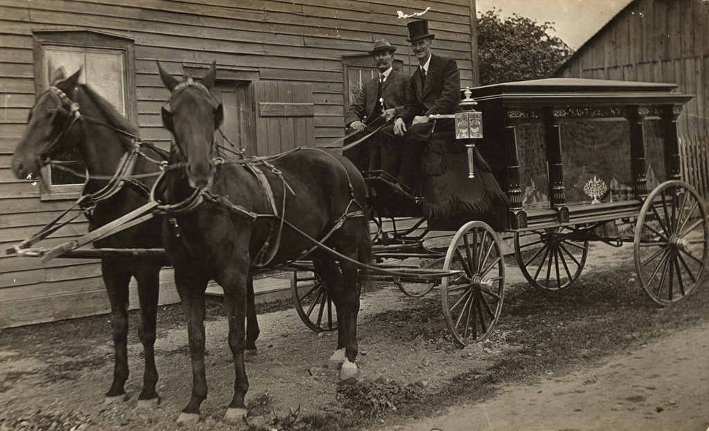 This is a picture of the hearse M950.1459.001. The men in it are Robert Bowers, the driver and William Sproul, the undertaker and owner of the hearse, in Dungannon, Ont.